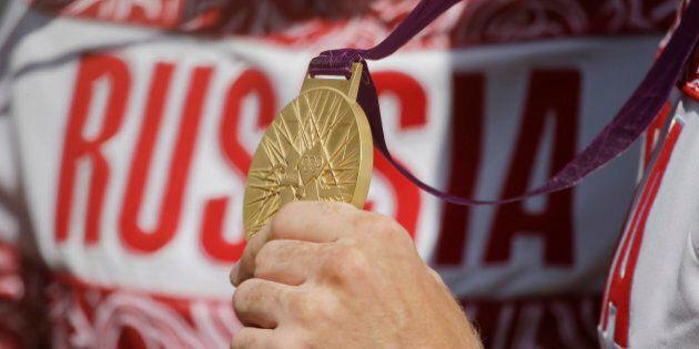 Russia's Alexander Dyachenko holds the gold medal he won in the men's kayak double 200m in Eton Dorney,...