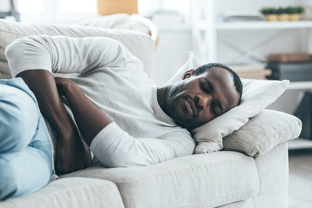 Handsome young African man keeping eyes closed while lying on the sofa and touching his stomach