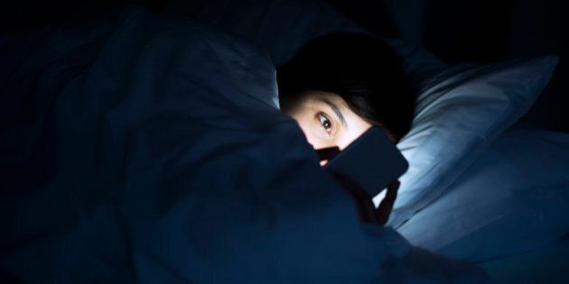 Woman using her phone under blanket in bed at night.