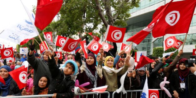 People wave national flags during celebrations marking the sixth anniversary of Tunisia's 2011 revolution...