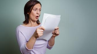 Shocking caucasian adult woman holding paper sheets and is surprised.