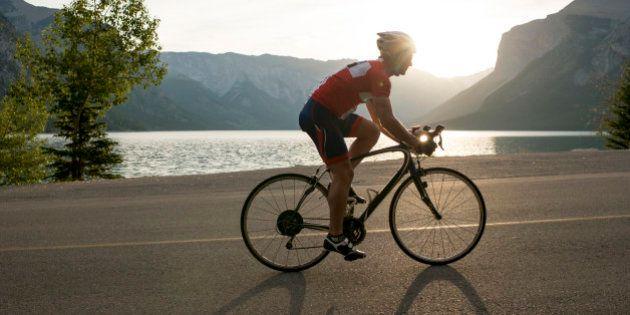 Road biker follows mountain road, sunrise