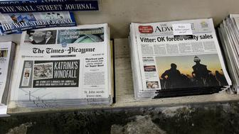 FILE - In this Thursday, Sept. 27, 2012 file photo, free introductory copies of the Baton Rouge Advocate's new New Orleans edition, right, are seen next to copies of the New Orleans Times-Picayune at Lakeside News in the New Orleans suburb of Metairie, La. The owners of Louisiana's The Advocate newspaper have purchased The Times-Picayune in New Orleans from Advance Local Media. The Advocate announced the purchase on its website Thursday, May 2, 2019.(AP Photo/Gerald Herbert)
