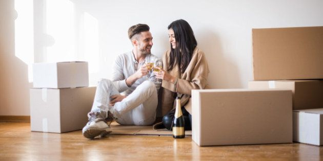 Young couple in love just moved in new apartment and having a toast on the floor before unpacking the boxes.