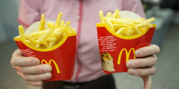 An employee holds two packets of french fries in this arranged photograph at McDonald's Corp.'s 505th...