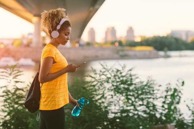 Latina Runner running in the city near river. Walking under the bridge, holding water bottle and typing on her smart phone. Carrying gym bag. Cityscape in background. Wearing big white headphones.