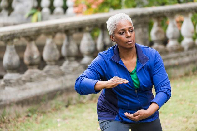 A senior African American woman in the park, practicing Tai Chi. She has a serious expression on her...