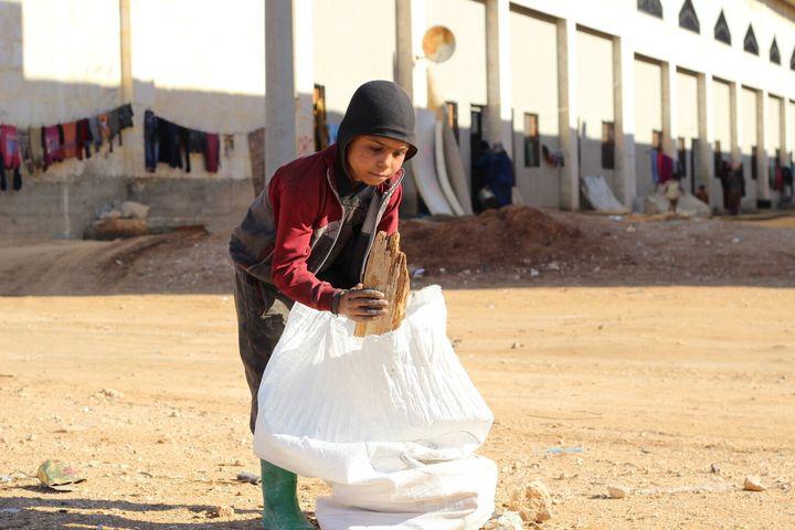Ahmed passe ses journées à ramasser du bois et tout ce qui peut être brûlé pour garder ses frères et ses sœurs au chaud.