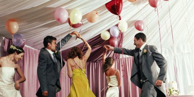 Bridal party dancing in marquee
