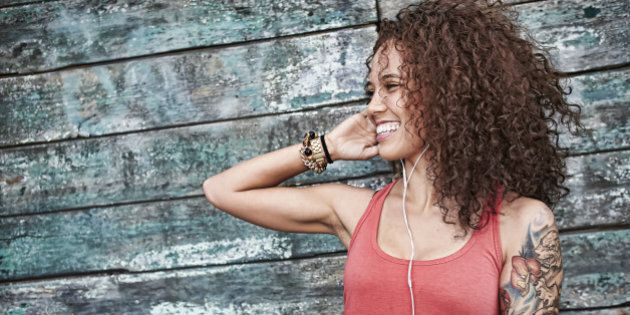Woman listening to mp3 player on city