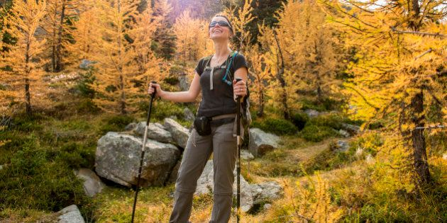 Hiker pauses on path in autumn
