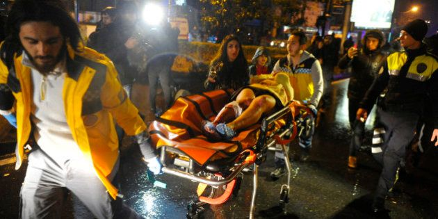 First aid officers carry an injured woman at the site of an armed attack on January 1, 2017 in Istanbul.At...