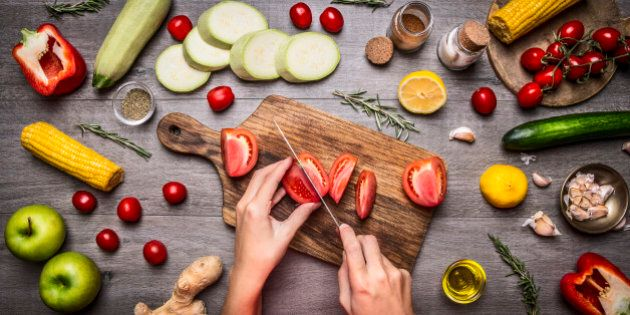Female hand cut tomatoes on rustic kitchen table, around lie ingredients, vegetables, fruits, and spices,...