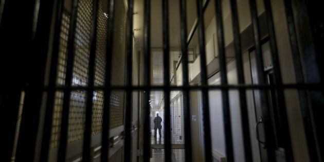 A guard stands behind bars at the Adjustment Center during a media tour of California's Death Row at...