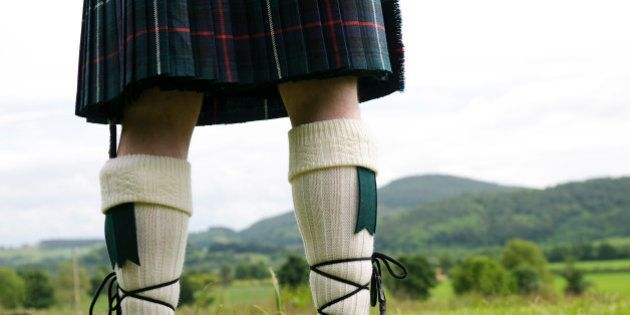 A Scotsman wearing a kilt, facing the hills of
