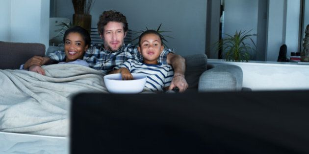 Multi-ethnic family having popcorn while watching TV in living room at