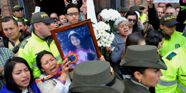 Mourners demand justice holding a picture of Yuliana - a seven-year-old girl who was raped, tortured...