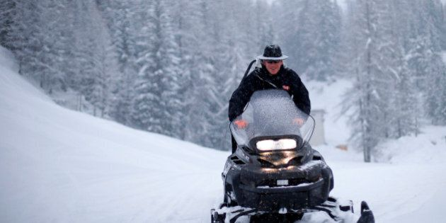 A course worker drives a snowmobile as the second training session of the Women's World Cup Downhill...
