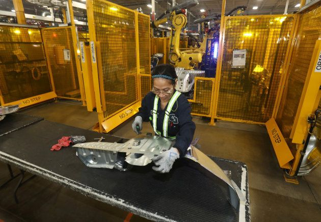 A worker checks welded part from auto weld assembly line at Alfield Industries, a subsidiary of Martinrea, one of three global auto parts makers in Canada, in Vaughan, Ont. April 28, 2017.