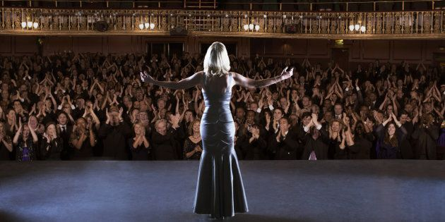 Performer standing with arms outstretched on stage in