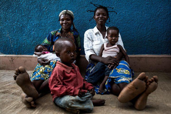 Deux mères et leurs enfants sont assises à l'extérieure d'une clinique soutenue par l'UNICEF, à Kananga.