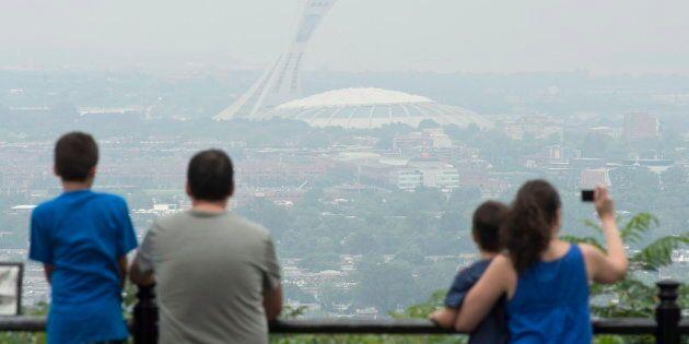 Des touristes photographient le Stade olympique à l'été 2013, un jour de