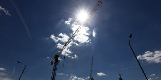 Construction cranes on residential building sites stand on the horizon in the Stratford district of London,...