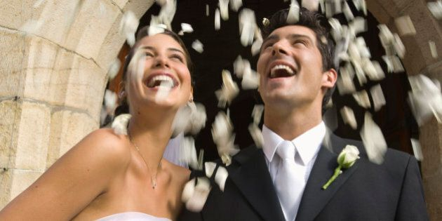 Flower petals over bride and groom