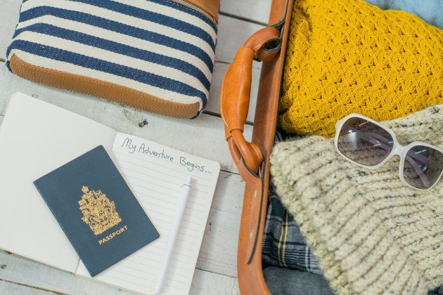 A series of travel items are prepared and laid out on a white wooden background. Included amongst these items are a notebook, wallet, purse, leather suitcase, passport, pen, sunglasses, and clothing. The items are ready for a vacation.