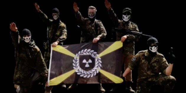 Des membres de la division Atomwaffen, un groupe néonazi violent, posent avec leur drapeau à thème