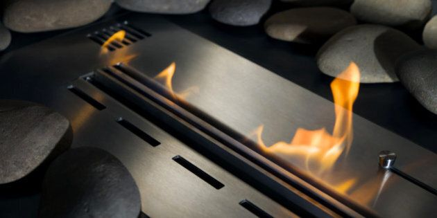 Bio-fireplace with fire, laid out around a smooth stone,