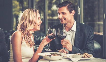 29540064 - cheerful couple in a restaurant with glasses of red wine