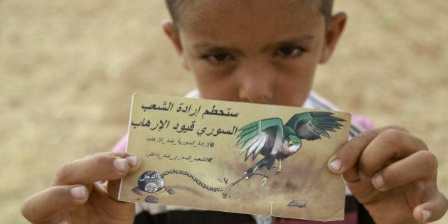 A young Syrian boy holds a banner dropped by a Syrian Democratic Forces (SDF) alliance plane reading in Arabic: 'The will of the Syrian people will break the chains of the terrorists' as US-backed Kurdish and Arab fighters advance into the Islamic State (IS) jihadist's group bastion of Manbij, in northern Syria, on June 23, 2016.Backed by air strikes by the US-led coalition bombing IS in Syria and Iraq, fighters with the Syrian Democratic Forces (SDF) alliance entered Manbij from the south, a monitoring group said. / AFP / DELIL SOULEIMAN (Photo credit should read DELIL SOULEIMAN/AFP/Getty Images)