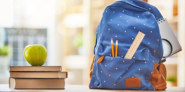 Back to school and happy time! Apple, pile of books and backpack on the desk at the elementary