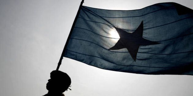 A policeman marches holding a Somali flag during a parade in Mogadishu, 11 December 2007. A roadside...