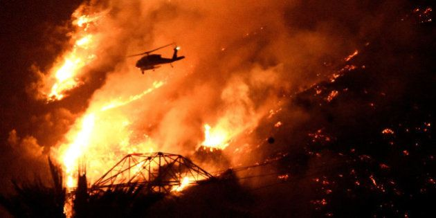 A Los Angeles County fire helicopter makes a night drop while battling the so-called Fish Fire above...