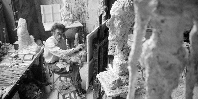 Giacometti en train de peindre dans son studio à Paris, en premier plan «La Grande Tête»,