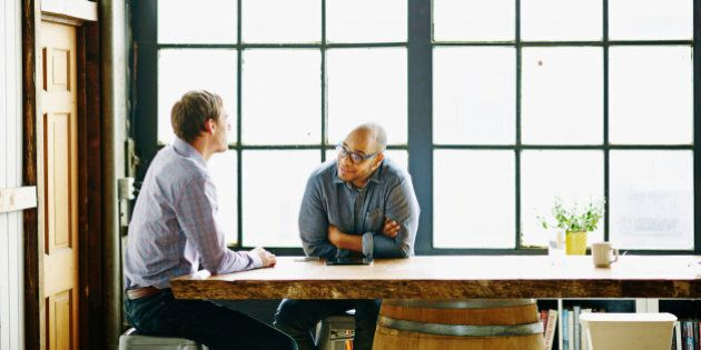 Smiling businessman in discussion with colleague at conference table in startup office