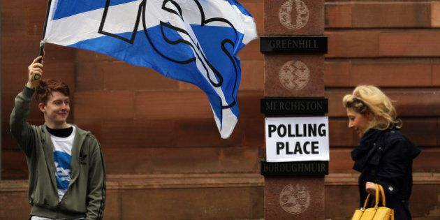 A voter in Scotland's Independence Referendum, right, walks past a YES supporter as she arrives at a...