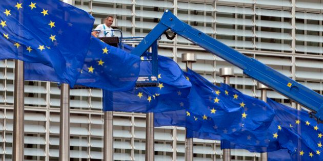 A worker on a lift adjusts the EU flags in front of EU headquarters in Brussels on Wednesday, June 22,...