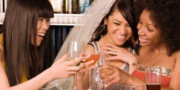 Multi-ethnic friends drinking in nightclub for bachelorette