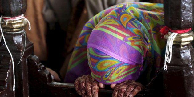 A woman prays at the shrine of Hasan-al-Maroof Sultan Manghopir, better known as the crocodile shrine,...