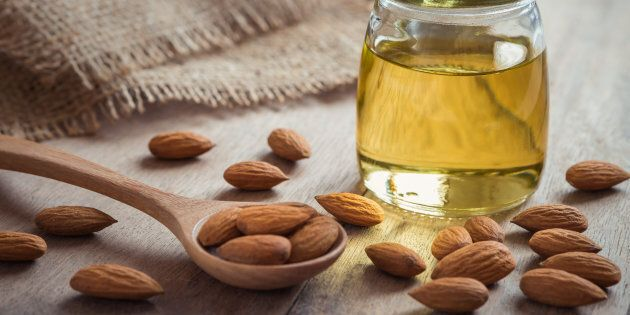 Almond oil in glass bottle and almonds on wooden
