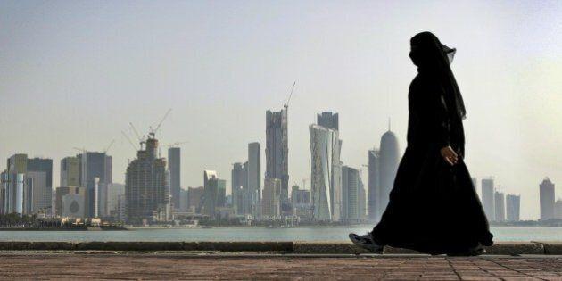 FILE- In this May 14, 2010 file photo, a Qatari woman walks in front of the city skyline in Doha, Qatar....