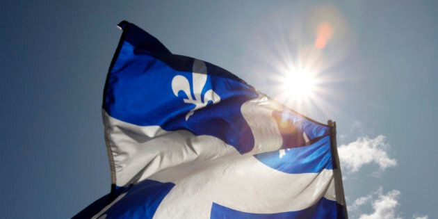 A Quebec flag flaps in the sky during the Moulin a Parole, a 24-hour long series of public readings,...