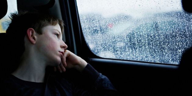 Young boy looking out rainy car