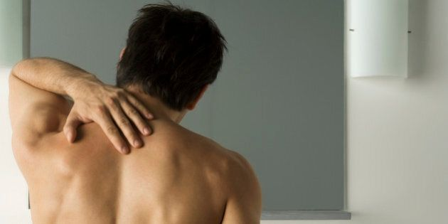 Bare-chested man touching his back, rear