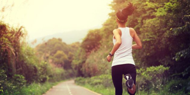 young fitness woman runner running at forest