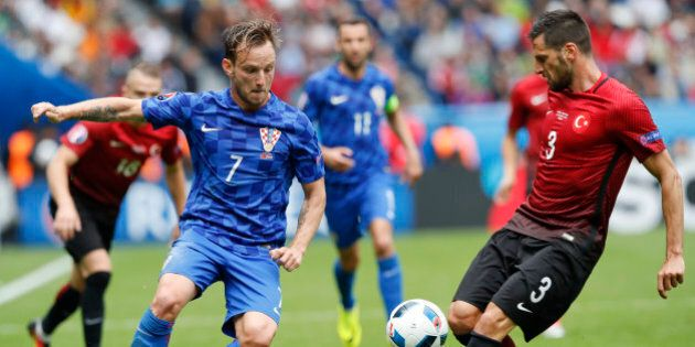 Croatia's Ivan Rakitic, left, and Turkey's Hakan Balta go for the ball during the Euro 2016 Group D soccer...
