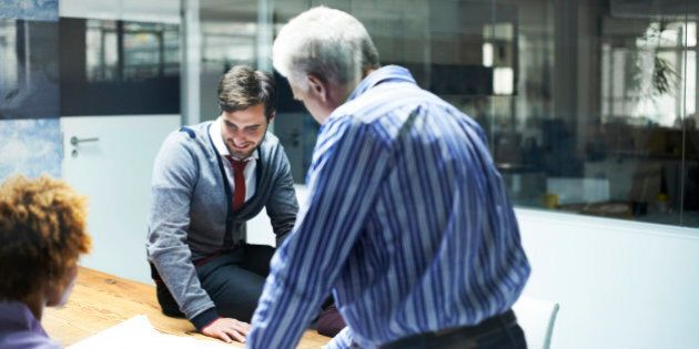 Mature businessman analyzing blueprint with colleagues in board room at office